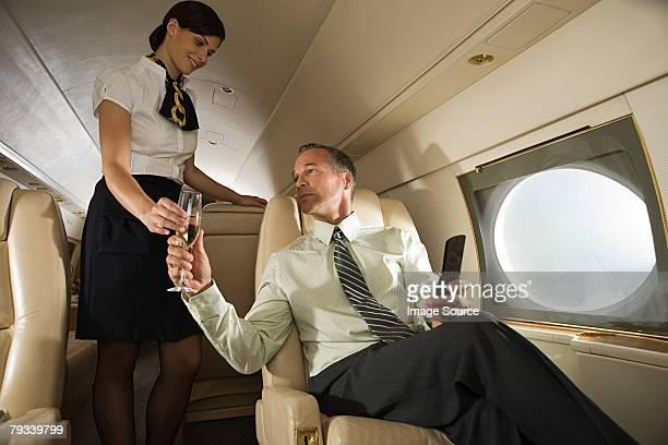 Stewardess handing champagne to man