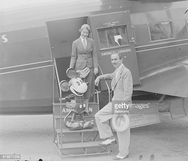 Stewardess Izola Readle takes tickets from cartoonist Walt Disney with his creation Mickey Mouse in Newark New Jersey as they board an airplane on...