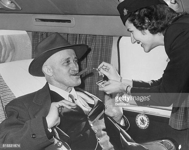 Stewardess Jane Driscoll lights a cigar for airline passenger Carl Graulein of East St. Louis, as he prepares to depart for his native Germany aboard...