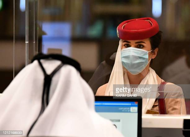 A stewardess of an Emirates Airlines flight from London arrives at Dubai International Airport on May 8 2020 amid the coronavirus Covid19 pandemic