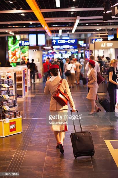 Stewardess of Emirates in duty free corridor of aiport Düsseldorf