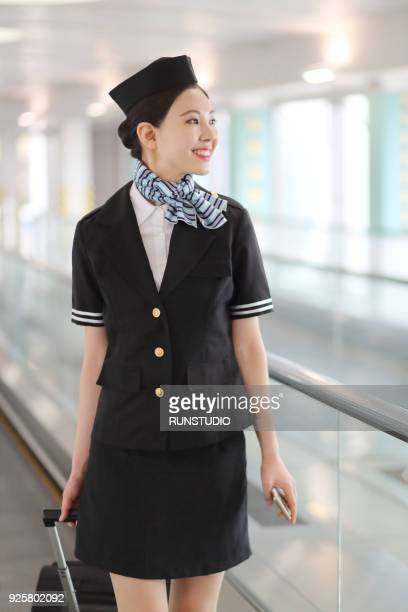 Stewardess On Moving Walkway At Airport