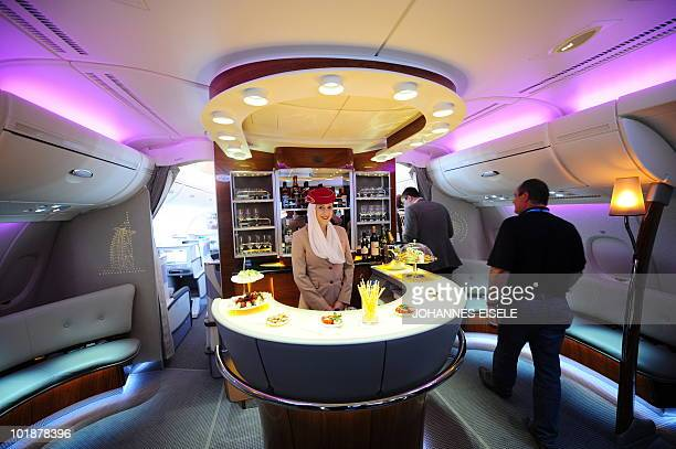 A stewardess poses inside the bar of an Emirates Airlines A380 aircraft presented at the International Aerospace Exhibition on June 8 2010 at the...