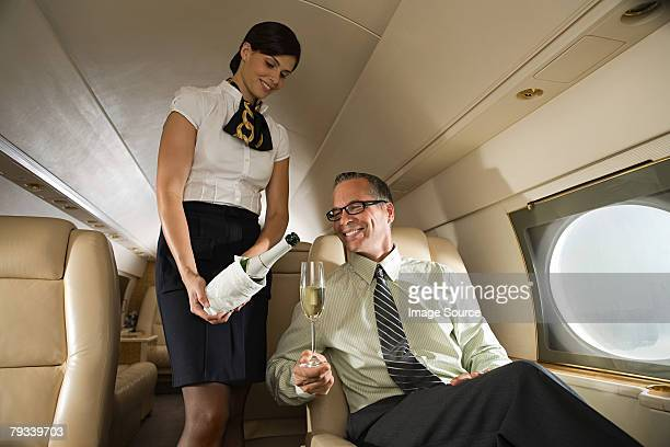 Stewardess pouring champagne for man