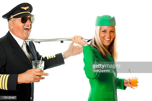 stewardess pulling pilot for his tie - aviation hat stock photos and pictures