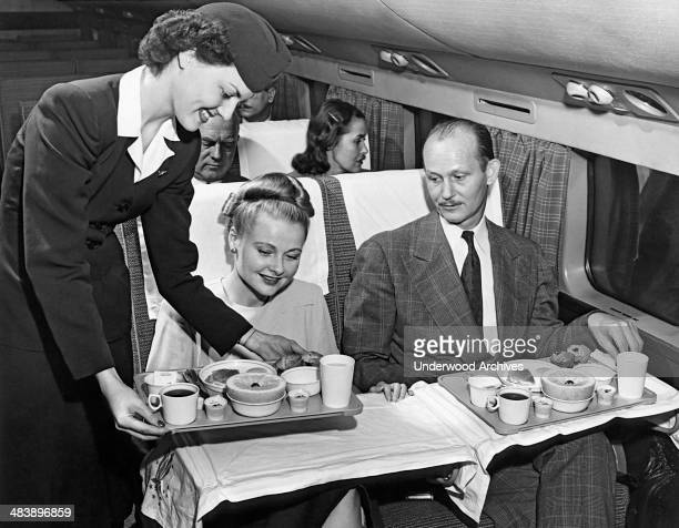 A stewardess serves a meal to a couple on an American Airlines flight mid to late 1950s