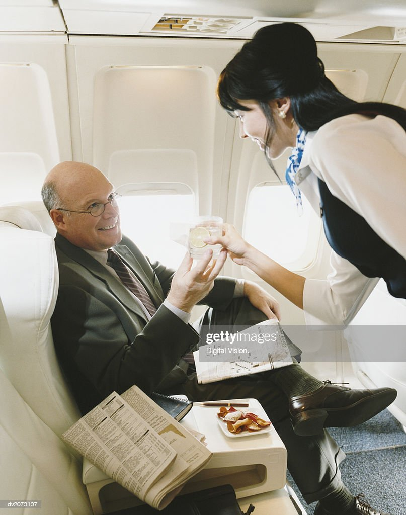 Stewardess Serving a Drink to a Businessman in an Aircraft : Stock Photo