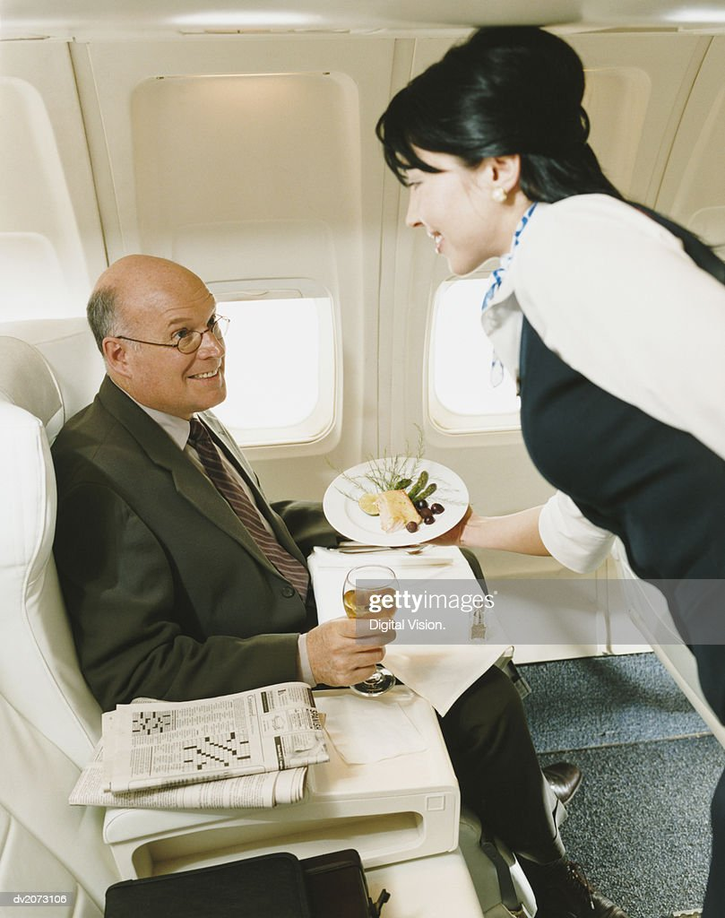 Stewardess Serving a Meal to a Businessman in an Aircraft : Stock Photo