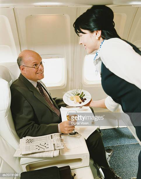 Stewardess Serving a Meal to a Businessman in an Aircraft