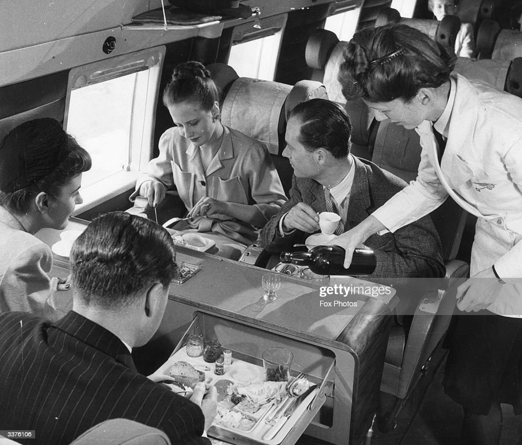 A stewardess serving drinks whilst passengers have lunch aboard a BEA Vickers Viking passenger plane.
