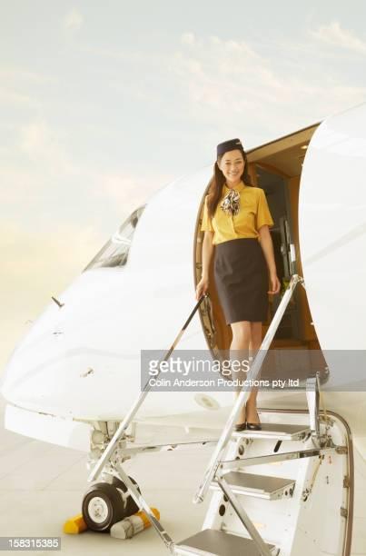 Stewardess standing in doorway of private jet
