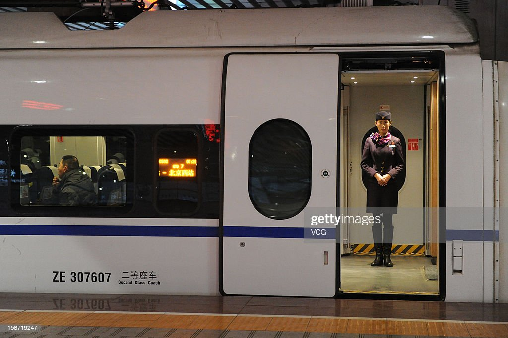 A stewardess stands at a doorway of a CRH high-speed train at Changsha South Railway Station on December 26, 2012 in Changsha, China. The world's longest high-speed rail route linking Beijing and Guangzhou started operation on Wednesday. Running at an average speed of 300 kilometers per hour, the 2,298-kilometer new route will cut the travel time between Beijing and Guangzhou from more than 20 hours to around eight.