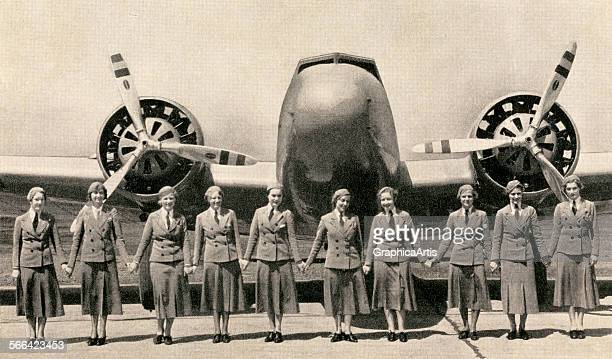 Stewardesses holding hands in front of a large twinpropeller commercial airplane screen print from a photograph 1940