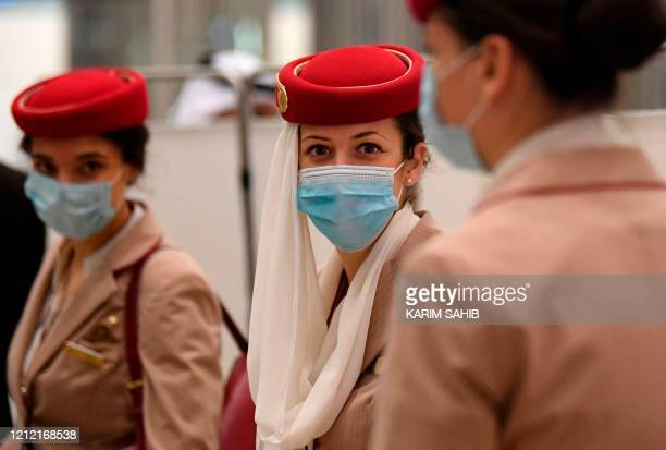 Stewardesses of an Emirates Airlines flight from London arrive at Dubai International Airport on May 8, 2020 amid the coronavirus Covid-19 pandemic.