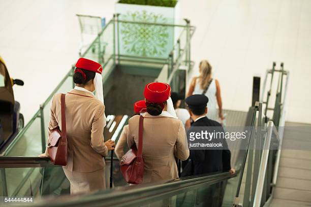 stewardesses of emirates on escalator - crew stock pictures, royalty-free photos & images