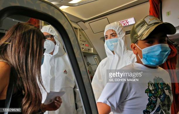 Stewardesses of Israir Airlines wearing full PPE prepare for take off from the Ben Gurion International Airport near the central Israeli city of Tel...