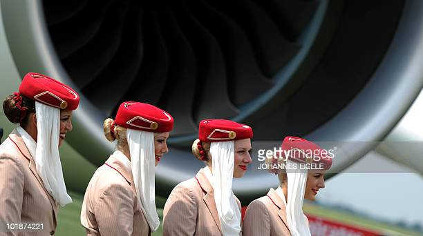 Stewardesses pose in front of an Emirates Airlines A380 aircraft at the International Aerospace Exhibition on June 8 2010 at the Schoenefeld airport...