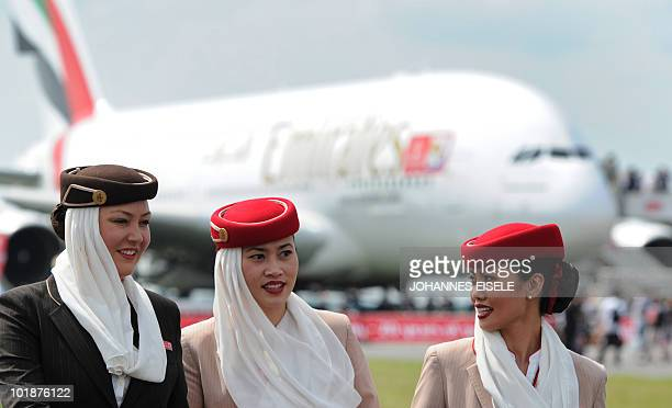 Stewardesses walk in front of an Emirates Airlines A380 aircraft at the International Aerospace Exhibition on June 8 2010 at the Schoenefeld airport...