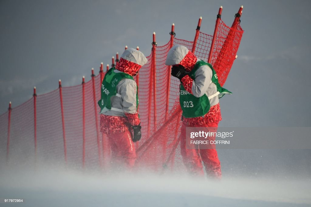 TOPSHOT - Stewards adjust a net as winds blow after the Alpine Skiing Women's Slalom was cancelled due to weather conditions at the Jeongseon Alpine Center during the Pyeongchang 2018 Winter Olympic Games in Pyeongchang on February 14, 2018. / AFP PHOTO / Fabrice COFFRINI