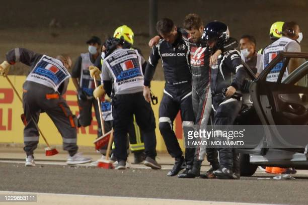 Stewards and medics attend to Haas F1's French driver Romain Grosjean after a crash at the start of the Bahrain Formula One Grand Prix at the Bahrain...