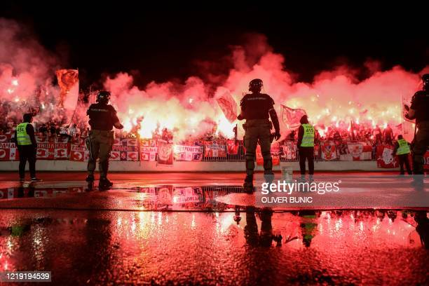 TOPSHOT Stewards and security personnel stand as Red Star supporters light flares during the Serbian Cup semifinal football match between FK Partizan...