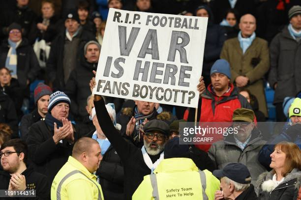 Stewards approach a spectator holding up a placard in the crowd against the use of the VAR during the English Premier League football match between...