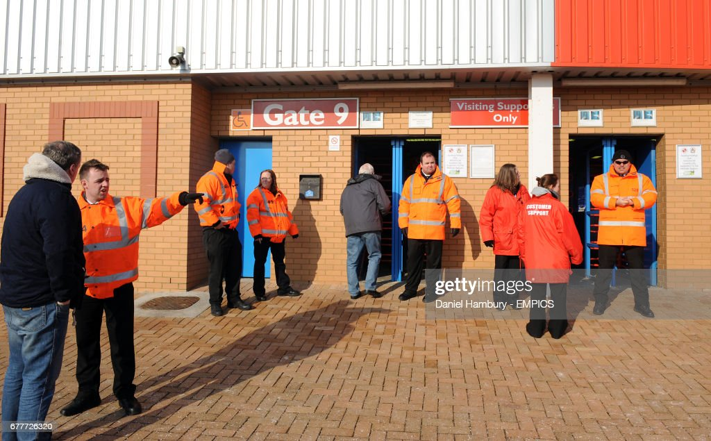 Stewards assist fans outside the ground before the game News