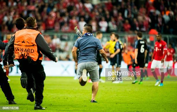 Stewards chase a pitch invader during the firstleg quarter final Champions league football match between Bayern Munich and Real Madrid at the Allianz...