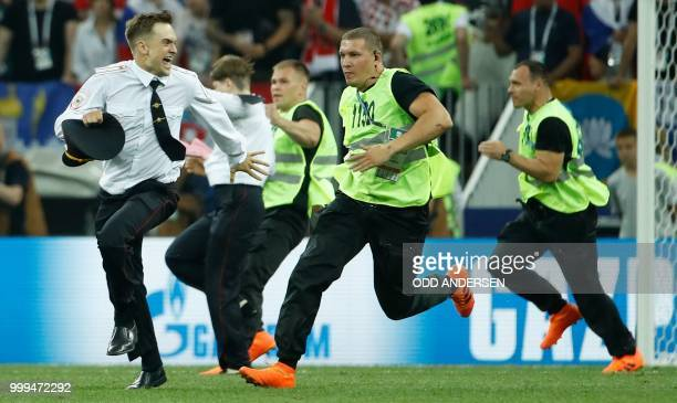 Stewards chase a pitch invader later identified as member of the Pussy Riot punk group Pyotr Verzilov during the Russia 2018 World Cup final football...