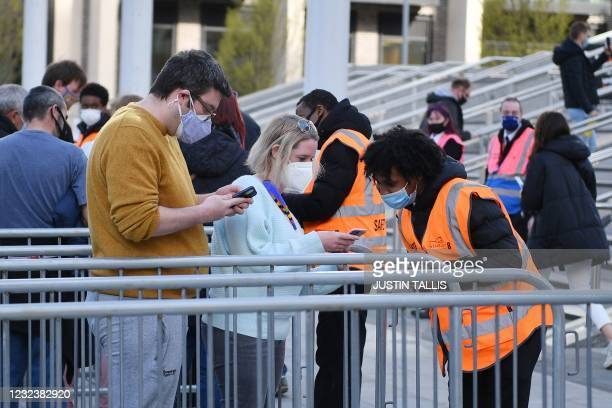 Stewards check the Covid-19 test results of spectators arriving at Wembley Stadium ahead of the English FA Cup semi-final football match between...