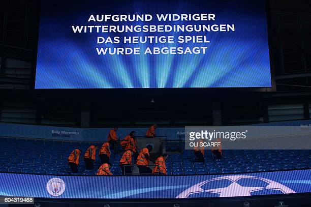 Stewards check the seats in the empty stands under an electronic screen displaying a message in German saying 'due to adverse weather conditions...