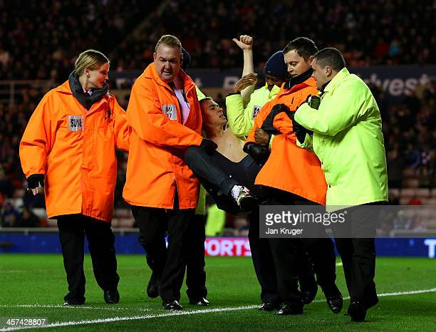 Stewards escort a pitch invader during the Capital One Cup Quarter-Final match between Sunderland and Chelsea at Stadium of Light on December 17,...