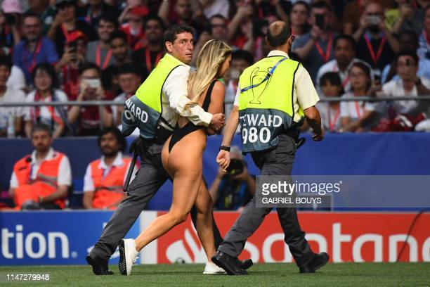 Stewards escort a pitch invader during the UEFA Champions League final football match between Liverpool and Tottenham Hotspur at the Wanda...