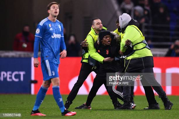 Stewards escort an intruder off the pitch during the UEFA Champions League round of 16 firstleg football match between Lyon and Juventus at the Parc...