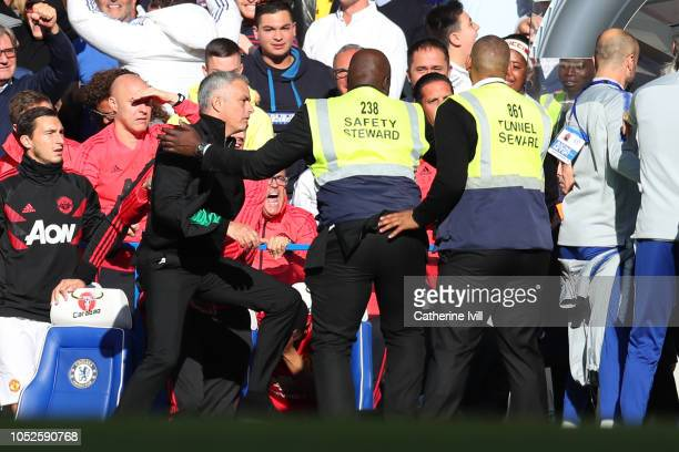 Stewards hold back Jose Mourinho Manager of Manchester United as he clashes with the Chelsea backroom staff during the Premier League match between...