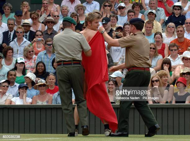 Stewards lead away a streaker who performed a cartwheel on the Centre Court at Wimbledon during the quarterfinal match between Russians Maria...