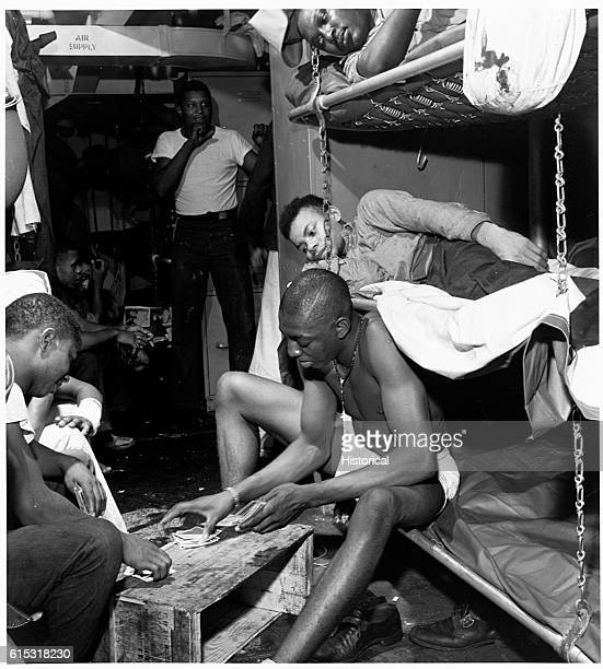 Stewards mates passing time the evening before battle at Manila with a card game in their bunk room November 1944 | Location Manila