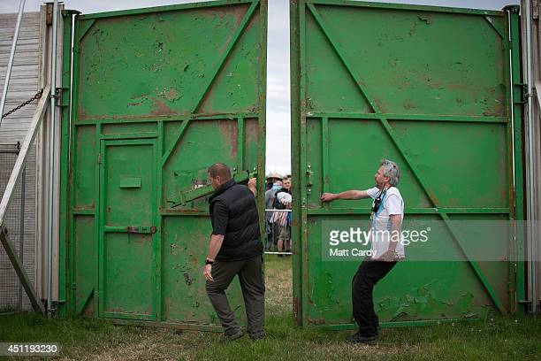 Stewards open the gates to ticket holders at Worthy Farm in Pilton on the first day of the 2014 Glastonbury Festival on June 25 2014 in Glastonbury...