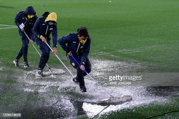 Stewards push out water from the pitch following heavy rains before the UEFA Europa League group I football match between Villarreal CF and Maccabi...