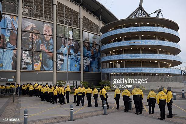 Stewards queue to enter the stadium ahead of the English Premier League football match between Manchester City and Liverpool at The Etihad stadium in...