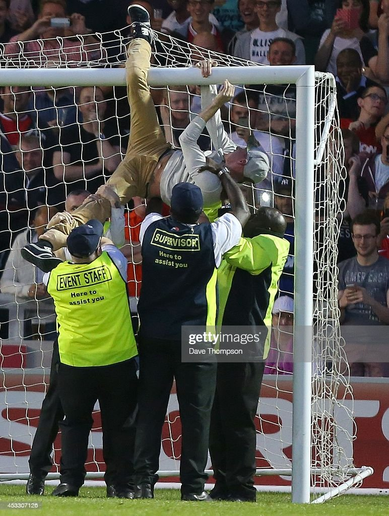 Stewards remove a fan from the crossbar during the match between Salford City and the Class of '92 XI at AJ Bell Stadium on August 7, 2014 in Salford, England.