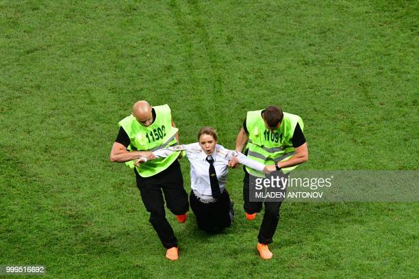 Stewards remove a pitch invader during the Russia 2018 World Cup final football match between France and Croatia at the Luzhniki Stadium in Moscow on...