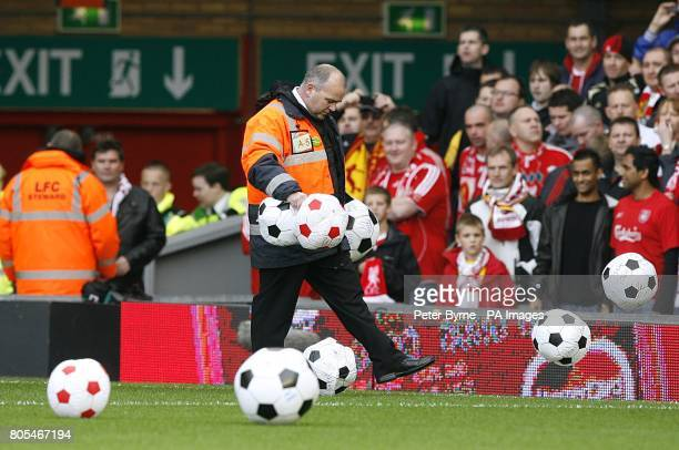 Stewards remove beach balls from the pitch at Anfield