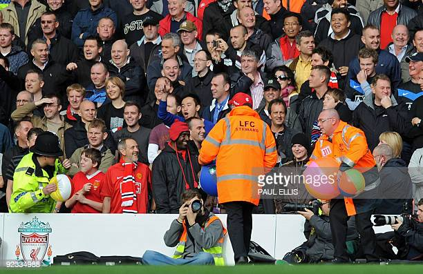 Stewards remove beach balls that had been thrown onto the pitch by supporters before the English Premier League football match between Liverpool and...