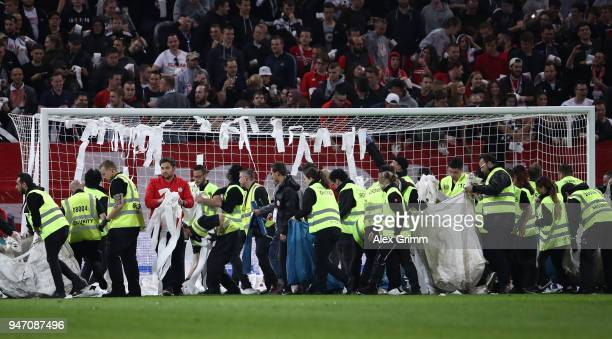 Stewards remove rolls of toilet paper thrown by fans during the Bundesliga match between 1 FSV Mainz 05 and SportClub Freiburg at Opel Arena on April...