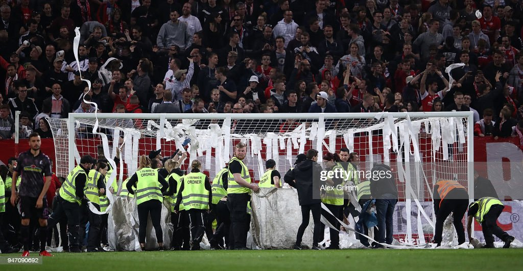 Stewards remove rolls of toilet paper thrown by fans during the Bundesliga match between 1. FSV Mainz 05 and Sport-Club Freiburg at Opel Arena on April 16, 2018 in Mainz, Germany.