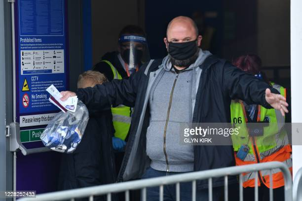Stewards search arriving supporters wearing face coverings ahead of the pre-season friendly football match between Brighton and Hove Albion and...