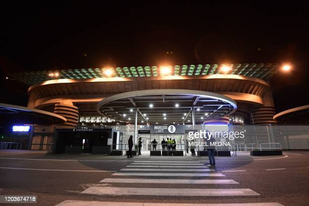 Stewards stand guard in front of the San Siro stadium closed to the public as a safety measure against the COVID19 the novel coronavirus ahead of the...