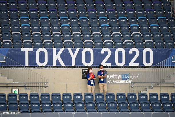 Stewards stand in the empty stands of the Oi Hockey Stadium's North pitch during the men's pool B match of the Tokyo 2020 Olympic Games field hockey...