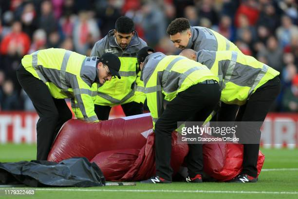 Stewards struggle to fold up the giant pitch banner before the Premier League match between Liverpool FC and Tottenham Hotspur at Anfield on October...